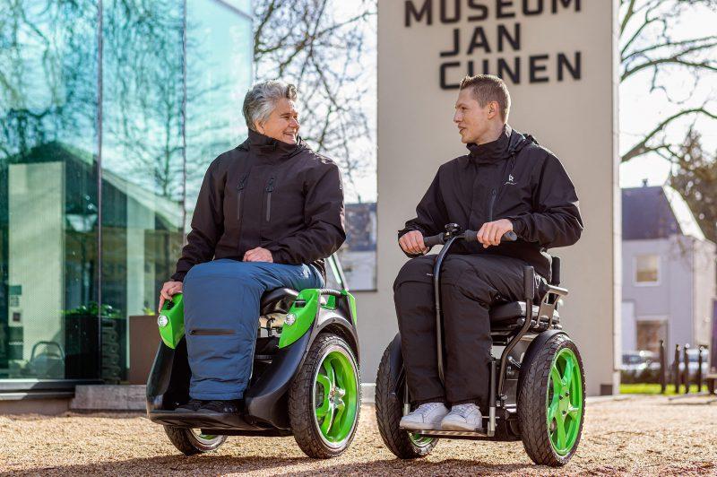 Bi-Go en Omeo balansrolstoel rijden samen door de stad.